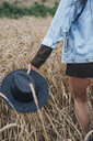 Young woman in corn field carrying black hat - VPIF00911