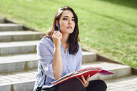 Portrait of pensive student with notebook sitting on stairs outdoors - JSMF00452
