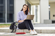 Portrait of smiling student sitting on stair outdoors working on laptop - JSMF00455