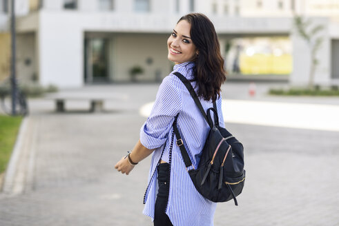 Portrait of smiling student with backpack on campus - JSMF00464