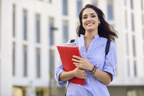 Portrait of smiling student with notebooks on campus - JSMF00467