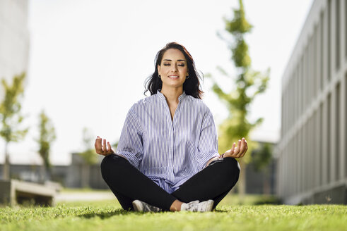 Portrait of student doing yoga exercices on campus - JSMF00473