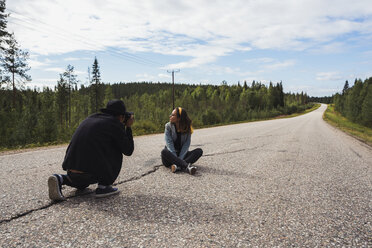 Finland, Lapland, man taking picture of woman sitting on empty country road - KKAF02080