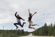 Finland, Lapland, exuberant young couple jumping in rural landscape - KKAF02083