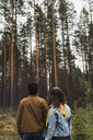 Finland, Lapland, rear view of young couple standing in rural landscape - KKAF02086