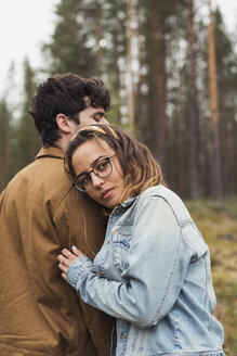 Finland, Lapland, young couple standing in rural landscape - KKAF02089