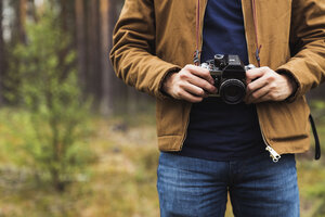 Finland, Lapland, close-up of man holding camera in rural landscape - KKAF02092