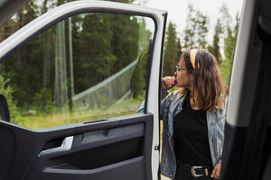 Finland, Lapland, young woman at a car in rural landscape - KKAF02098