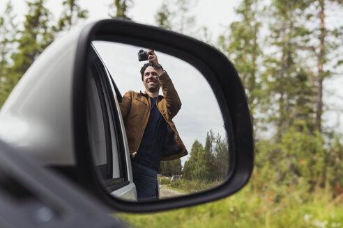 Finland, Lapland, wing mirror reflection of man taking picture out of a car - KKAF02101