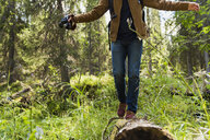 Finland, Lapland, man balancing on log in forest - KKAF02104
