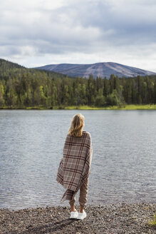 Finland, Lapland, woman wrapped in a blanket standing at the lakeside - KKAF02110