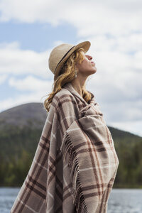Finland, Lapland, woman wearing a hat wrapped in a blanket standing at the lakeside - KKAF02113