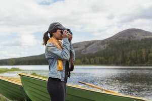 Finland, Lapland, woman taking picture with a camera at the lakeside - KKAF02119