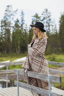 Finland, Lapland, woman wearing a hat wrapped in a blanket standing on jetty at the lakeside - KKAF02122