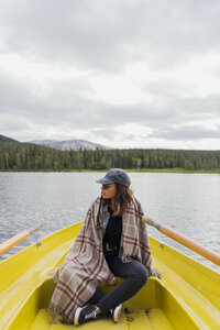 Finland, Lapland, woman wearing a blanket on a boat on a lake - KKAF02125