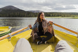 Finland, Lapland, woman wearing a blanket in a rowing boat on a lake - KKAF02128