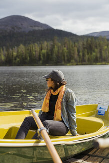Finland, Lapland, woman sitting in a boat on a lake - KKAF02131