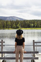 Finland, Lapland, woman wearing a hat  standing on jetty at a lake - KKAF02134