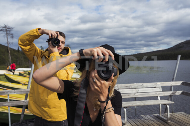 Finland, Lapland, man and woman taking pictures on jetty at a lake - KKAF02137 - Kike Arnaiz/Westend61