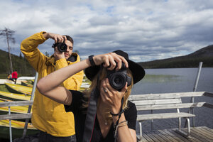 Finland, Lapland, man and woman taking pictures on jetty at a lake - KKAF02137