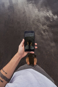Man taking a cell phone picture with feet in water of a lake - KKAF02140