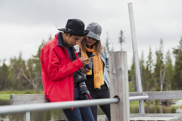 Finland, Lapland, couple on jetty at a lake using cell phone - KKAF02146