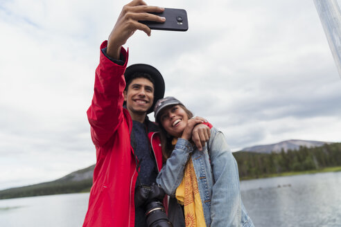 Finland, Lapland, happy couple taking a selfie at a lake - KKAF02149