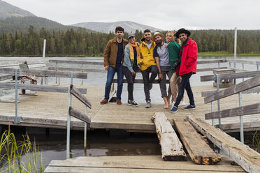 Finland, Lapland, portrait of friends standing on jetty at a lake - KKAF02158