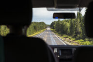 Finland, Lapland, interior view of man driving car in rural landscape - KKAF02161
