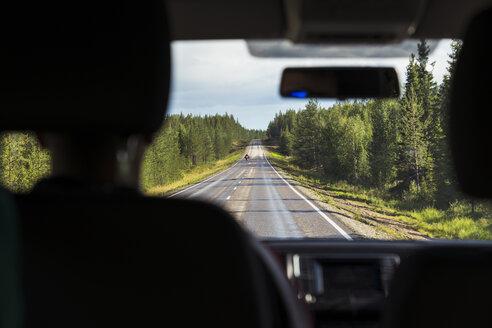 Finland, Lapland, interior view of man driving car in rural landscape - KKAF02161