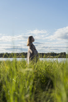 Finland, Lapland, woman wrapped in a blanket standing at the lakeside - KKAF02164
