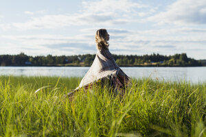 Finland, Lapland, woman wrapped in a blanket standing at the lakeside - KKAF02167