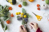 Autumnal decoration, ornamental pumpkins, woman's hand binding bunch of flowers - JUNF01327