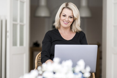Portrait of smiling blond mature woman using laptop at home - FMKF05292