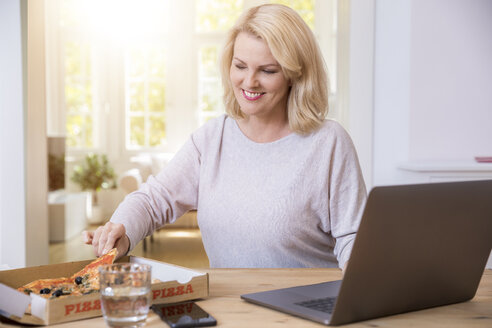 Portrait of smiling blond mature woman at home office eating pizza - FMKF05304