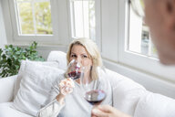 Portrait of blond mature woman drinking red wine with her partner at home - FMKF05313