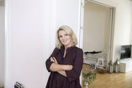 Portrait of smiling blond mature woman at home - FMKF05316