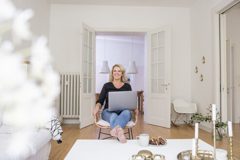 Portrait of smiling blond mature woman using laptop at home - FMKF05319