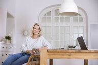 Portrait of smiling blond mature woman with smartphone and laptop at home - FMKF05322