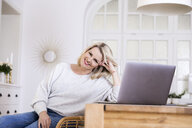 Portrait of smiling blond mature woman with laptop at home - FMKF05325