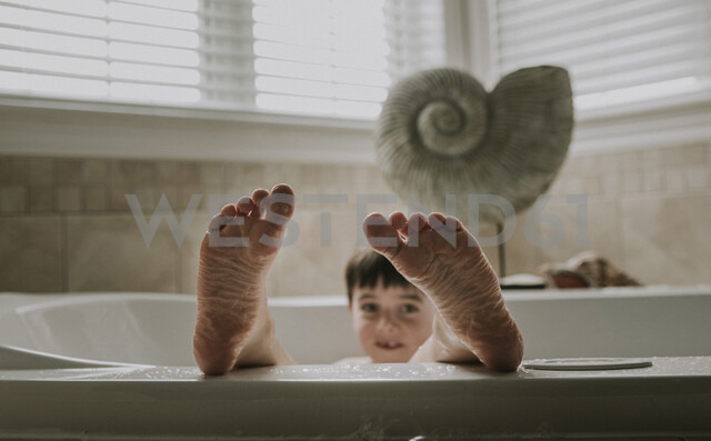 Portrait of boy taking bath in bathtub - CAVF48998