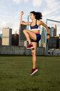 Female athlete jumping on grassy field against sky - CAVF49055