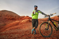 Hiker holding drink while standing by mountain bike at desert during sunset - CAVF49094