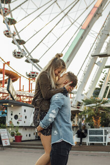 Happy young couple embracing and kissing at a funfair - LHPF00090