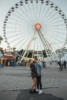 Young couple in love, kissing and embracing at a funfair - LHPF00093