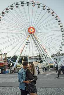 Young couple in love, embracing at a funfair - LHPF00108