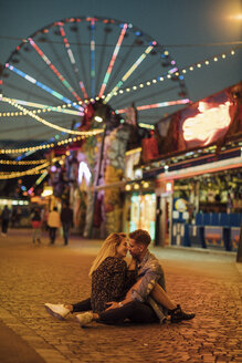Happy young couple embracing and kissing at a funfair - LHPF00111