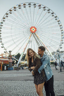 Young couple in love, embracing at a funfair - LHPF00114