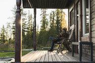 Young man sitting on veranda of a wood house, playing the ukulele - KKAF02174