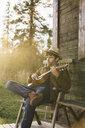 Young man sitting on veranda of a wood house, playing the ukulele - KKAF02177